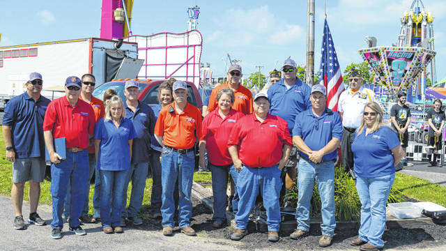 Members of the Fairboard gather Saturday morning around the flag pole during the official start of the 2019 Clinton County Fair.