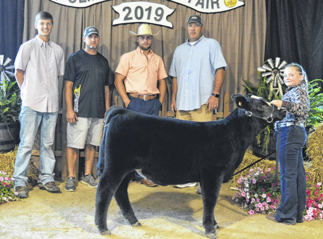 The grand champion feeder heifer is exhibited by Taylor Barton, right, in the Open Steer, Heifer, Feeder Calf Show. The heifer weighed 381 pounds. The show judge, Tyler Clark, has a cowboy hat.