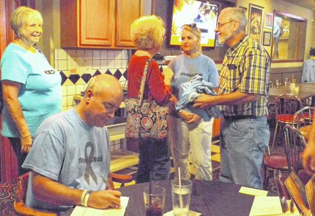 At left foreground Brian Mudd signs a copy of his book at Mac D's Pub during a Thursday event. His wife Tammy is standing in the background second from the right.
