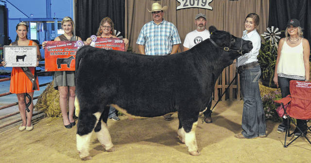 Maggie Mathews, second from right, exhibited the 1,231-pound steer that was chosen the Reserve Champion Market Beef entry in the Junior Fair Steer, Market Heifer & Feeder Calf Show. Fair Princesses Carrie Robinson and Paris Eades are pictured on the left.