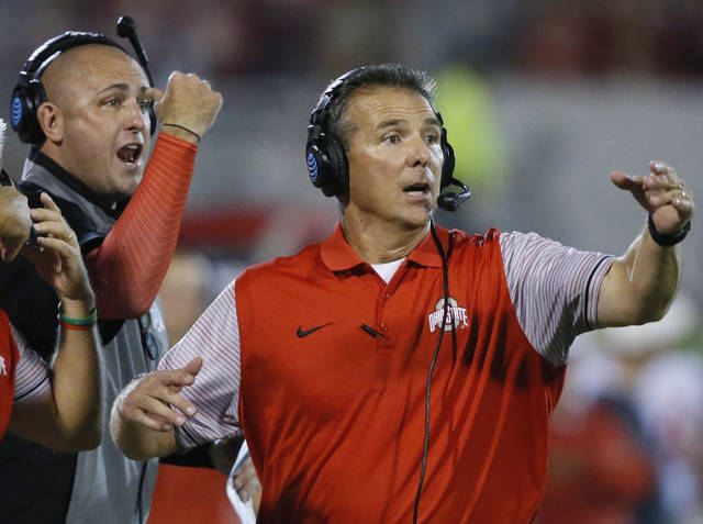 FILE - In this Sept. 17, 2016, file photo, Ohio State coach Urban Meyer, right, and assistant coach Zach Smith, left, gesture from the sideline during the team's NCAA college football game against Oklahoma in Norman, Okla. Meyer encouraged Smith to stay with the Buckeyes in January 2018 after the then-assistant coach was pursued by Alabama, according to texts messages from Meyer to Smith. On Friday, Aug. 2, 2019, Ohio State released thousands of pages of heavily redacted texts and email that were part of an external investigation conducted last August into Meyer's handling of Smith and what he knew about allegations of domestic violence made by Smith's ex-wife, Courtney Smith. Meyer was suspended for the first three games of last season by Ohio State after the investigation. After the season he retired at 54, citing health concerns. He is now working as an analyst with Fox Sports. (AP Photo/Sue Ogrocki, File)