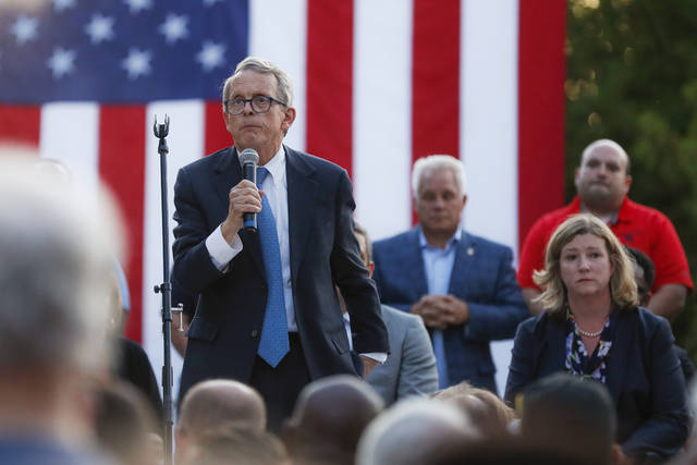 Ohio Gov. Mike DeWine, left, speaks alongside Dayton Mayor Nan Whaley, right, during a vigil at the scene of a mass shooting, Sunday, Aug. 4, 2019, in Dayton, Ohio. A masked gunman in body armor opened fire early Sunday in the popular entertainment district in Dayton, killing several people, including his sister, and wounding dozens before he was quickly slain by police, officials said. (AP Photo/John Minchillo)