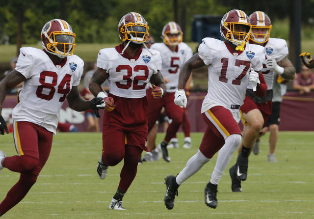 FILE - In this Aug. 5, 2019, file photo, Washington Redskins wide receiver Terry McLaurin (17) runs drills with teammates Samaje Perine (32) and Darlin Kidsy Jr., (84) during the Washington Redskins NFL football training camp in Richmond, Va. The Redskins will become the first NFL team to have a gambling-focused telecast of their games, offering cash prizes to viewers who correctly predict in-game outcomes during the preseason. The telecasts on the regional cable network NBC Sports Washington will follow a formula established by the Redskins' NBA neighbors, the Washington Wizards. (AP Photo/Steve Helber, File)