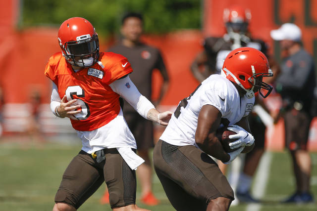 "FILE - In this Aug. 5, 2019, file photo, Cleveland Browns quarterback Baker Mayfield (6) hands off to running back Nick Chubb (24) during practice at the NFL football team's training facility, in Berea, Ohio. Despite an embarrassment of offensive weapons, including Baker Mayfield and Odell Beckham Jr., Browns coach Freddie Kitchens made it clear his team won't be ""pass happy"" this season. Not as long as he's got Nick Chubb, who ran for 996 yards as a rookie and could be on the verge of becoming one of the NFL's top backs. (AP Photo/Ron Schwane, File)"