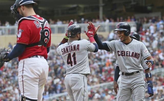 Cleveland Indians' Carlos Santana, center, is welcomed by pinch runner Oscar Mercado, right's Santana scores on his grand slam off Minnesota Twins pitcher Taylor Rogers in the 10th inning of a baseball game Sunday, Aug. 11, 2019, in Minneapolis. The Indians won 7-3. At left is Twins catcher Mitch Garver. (AP Photo/Jim Mone)