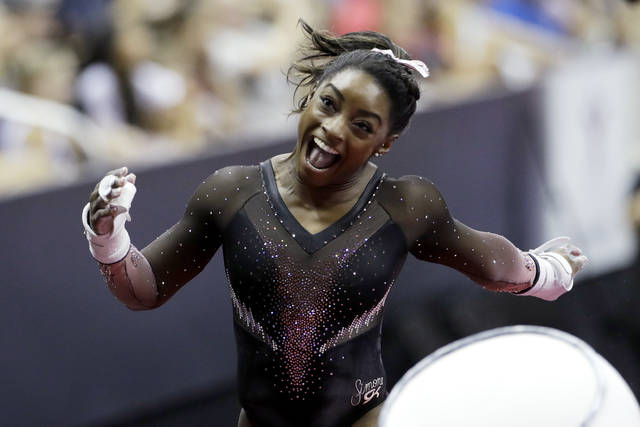 Simone Biles celebrates after competing in the uneven bars to win the all around senior women's competition at the 2019 U.S. Gymnastics Championships Sunday, Aug. 11, 2019, in Kansas City, Mo. (AP Photo/Charlie Riedel)