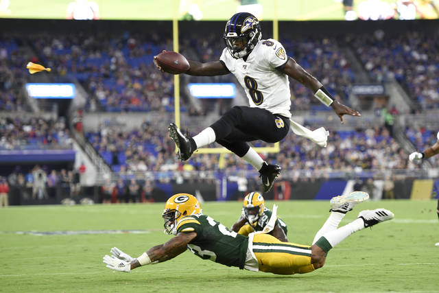 Baltimore Ravens quarterback Lamar Jackson (8) leaps over Green Bay Packers cornerback Jaire Alexander (23) during the first half of a NFL football preseason game, Thursday, Aug. 15, 2019, in Baltimore. The play was called back on a penalty on the Ravens. (AP Photo/Gail Burton)