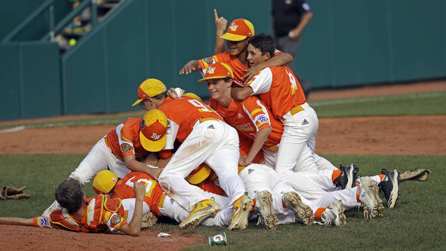 River Ridge, Louisiana's Stan Wiltz embraces Peyton Spadoni (6) as they jump on top of Jeffrey Curtis and Conner Perrot (9) on top of the pile as they celebrate the 8-0 win against Curacao in the Little League World Series Championship game in South Williamsport, Pa., Sunday, Aug. 25, 2019. (AP Photo/Tom E. Puskar)