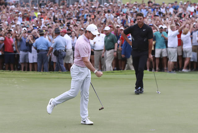 Rory McIlroy pumps his fist, the patrons cheer, and Brooks Koepka looks as as the birdie putt drops to win the Tour Championship golf tournament and The FedEx Cup Sunday, Aug. 25, 2019, at East Lake Golf Club in Atlanta. (Curtis Compton/Atlanta Journal-Constitution via AP)