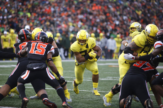 FILE - In this Friday, Nov. 23, 2018 file photo ,Oregon running back C.J. Verdell, center, and Oregon State safety Jeffrey Manning Jr. (15) during an NCAA college football game in Corvallis, Ore. College football starts better than it ends. The sport has evolved through numerous postseason systems that have clumsily crowned champions, and while the College Football Playoff does a better job than its predecessors it has also spawned a month's worth of tedious debate over the meaningfulness of bowl games. (AP Photo/Timothy J. Gonzalez, File)