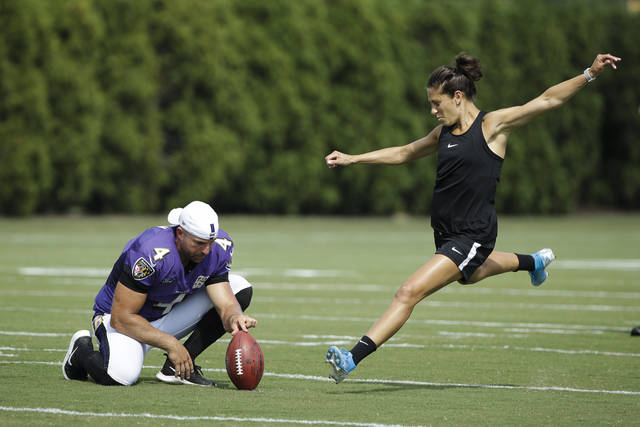 Baltimore Ravens' Sam Koch holds the ball for United States soccer player Carli Lloyd as she attempts to kick a field goal after the Philadelphia Eagles and the Baltimore Ravens held a joint NFL football practice in Philadelphia, Tuesday, Aug. 20, 2019. (AP Photo/Matt Rourke)