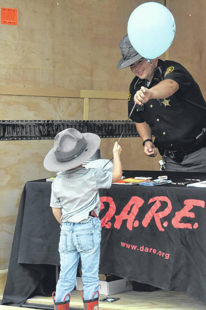 At last year's event, Bryden Priest gets a balloon from Clinton County Sheriff's Deputy and D.A.R.E Officer David Boris.