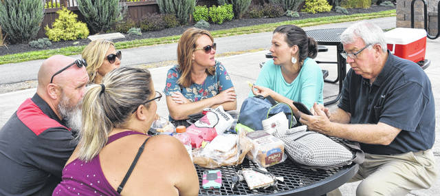 From left, Jason Stoops, Kristi Fickert, Leah Lorenz, Ruth Brindle, Marian Miller, and Mark McKay enjoy their lunches at Xidas Park at the Picnic in the Park on Thursday.