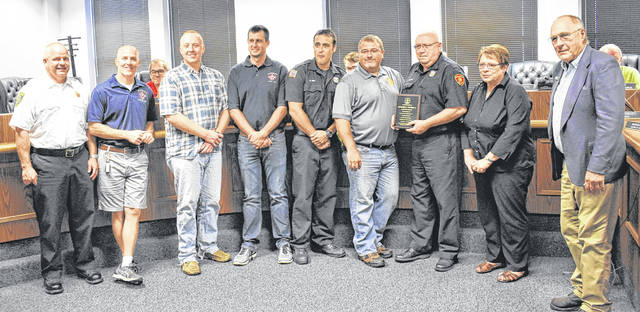 Retiring Wilmington FD Lt. Marvin Corbin, third from the right, stands beside his wife, along with Mayor John Stanforth and Corbin's fellow firefighters at Thursday's Wilmington City Council, meeting where he was honored for his 25 years of service.