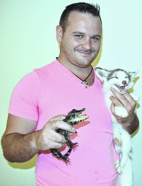 A resource fair at Blanchester Friends Housing included animals from the Bone Family Exotic Farm. Pictured is Brian Bone, holding a dwarf caiman crocodile and a fox. Also there were a marmoset monkey and a Brazilian short-tailed possum. Blanchester Friends Housing is an Episcopal Retirement Services-managed senior housing community. The resource fair was tailored for the residents, and included booths staffed by representatives of Council on Aging of Southwestern Ohio, insurance companies, a shop that provides diabetic and orthopedic shoes and compression socks, a local funeral home, a pharmacy, a homecare provider, and a long-term care facility. Food items for a barbecue held later were provided by Continental Manor and Humana.