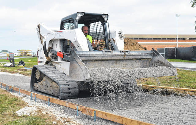 As part of a major construction project, Phase 1 work is in full gear Thursday at the Laurel Oaks Career Campus in Wilmington. Phase 2 is anticipated to begin in November, said a spokesperson on site. The project will include new lab and classroom space and an expanded cafeteria, as well as a new addition to connect the two main existing buildings. The worker pictured is spreading a gravel base for a new sidewalk that will redirect pedestrian traffic.