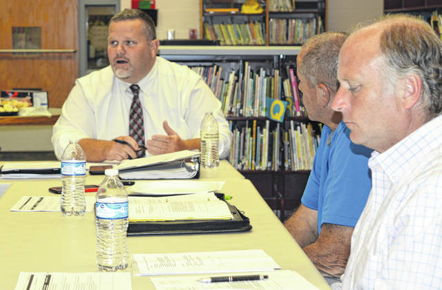 East Clinton Supt. Eric Magee, center background, reports to the board Tuesday night. Clockwise are board members Tim Starkey and Greg Bronner.