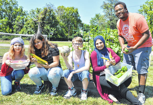 "Clinton County Youth Council's (CCYC) summer schedule had a gardening activity. Among the participants are, from left, Nevah Wilson, Elizabeth Floyd, Leo Baker, intern Zuley Aslanova, and support staff Darrian Cole. Scilla Wahrhaftig, a Master Gardener of Wilmington, helped with the horticultural education of the young gardeners. Youth have harvested green beans, tomatoes, cucumbers, cantaloupes, banana peppers, jalapenos, bell peppers, peas and zucchini. With the start of school, CCYC will resume its after-school programming, including the ""Academic Success Program."" CCYC is the county's only free after-school youth center. It provides academic support, positive programming, and mentoring for youth in grades 6 to 12. It's located at 302 West Sugartree Street in Wilmington."