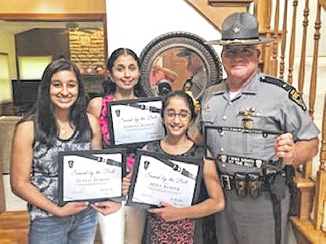 Bhavna Kumar, Sonali Kumar and Mira Kumar are recognized by Lt. Stan Jordan of the Ohio State Highway Patrol Wilmington Post.
