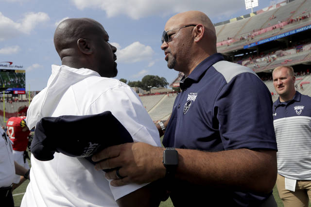 Maryland head coach Michael Locksley, left, shakes hands with Howard head coach Ron Prince after an NCAA college football game, Saturday, Aug. 31, 2019, in College Park, Md. Maryland won 79-0. (AP Photo/Julio Cortez)