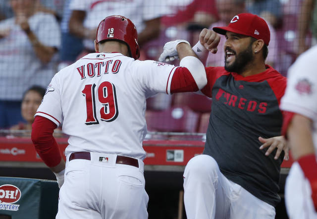 Cincinnati Reds' Joey Votto (19) is congratulated for his solo home run off Philadelphia Phillies starting pitcher Aaron Nola by Eugenio Suarez during the first inning of a baseball game Wednesday, Sept. 4, 2019, in Cincinnati. (AP Photo/Gary Landers)