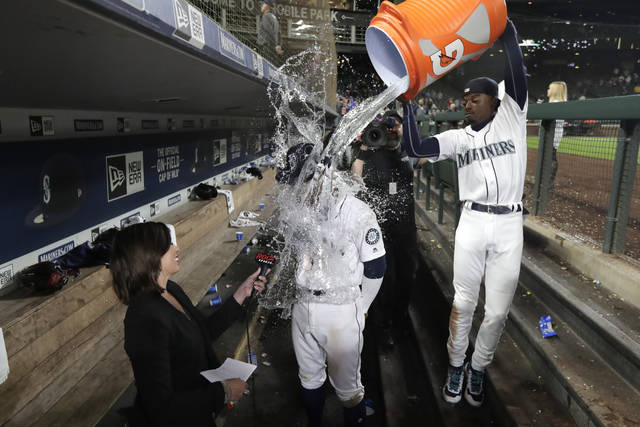 Seattle Mariners right fielder Kyle Lewis, center, is doused with water by Dee Gordon, right, as Lewis takes part in an interview following the team's baseball game against the Cincinnati Reds, Tuesday, Sept. 10, 2019, in Seattle. Lewis hit a solo home run in his major league debut as the Mariners won 4-3. (AP Photo/Ted S. Warren)
