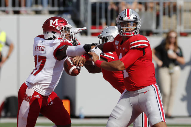 Miami (Ohio) linebacker Myles Reid, left, knocks the ball away from Ohio State quarterback Justin Fields, causing a fumble and a safety, during the first half of an NCAA college football game Saturday, Sept. 21, 2019, in Columbus, Ohio. (AP Photo/Jay LaPrete)