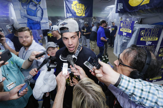 Milwaukee Brewers right fielder Christian Yelich speaks to reporters in the clubhouse after the Brewers clinched a playoff berth with a 9-2 win over the Cincinnati Reds in a baseball game Wednesday, Sept. 25, 2019, in Cincinnati. (AP Photo/John Minchillo)