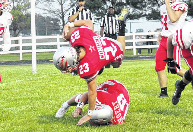 East Clinton's Isaiah Conger (23) goes flying over teammate Kaleb Kingery in the end zone during last week's game against Cedarville.