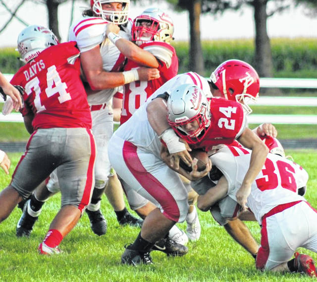 East Clinton's Todd Wedding (24) fights for yardage as Phillip Davis (74) and Kaleb Kingery (18) block against Hillsboro in last week's game.