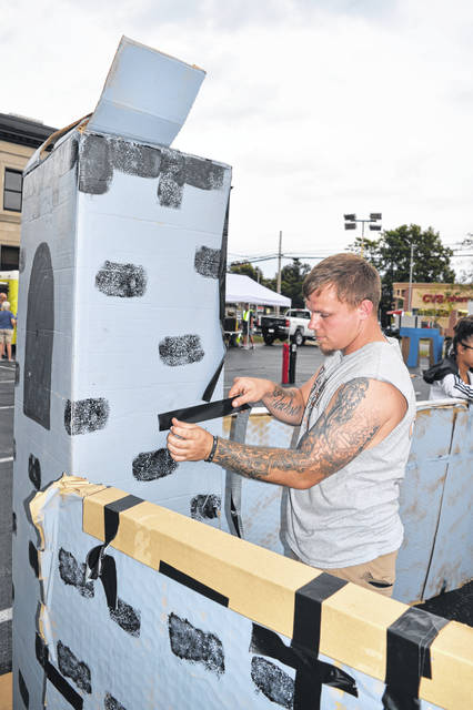 Damian Tomlinson helps build a tower as part of the Wilmington Church of God's structure in Cardboard City.