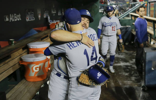 Los Angeles Dodgers catcher Russell Martin (55) and second baseman Enrique Hernandez (14) embrace in the dugout after Game 3 of the baseball team's National League Division Series against Washington Nationals on Sunday, Oct. 6, 2019, in Washington. The Dodgers won 10-4. (AP Photo/Julio Cortez)