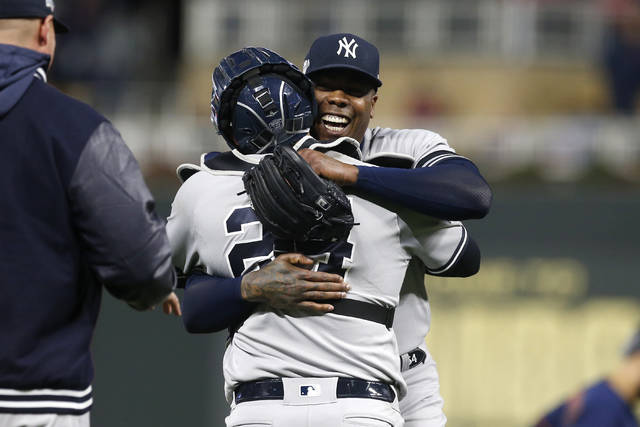 New York Yankees relief pitcher Aroldis Chapman, right, celebrates with teammate Gary Sanchez after their team's 5-1 victory over the Minnesota Twins in Game 3 of a baseball American League Division Series, Monday, Oct. 7, 2019, in Minneapolis. (AP Photo/Jim Mone)