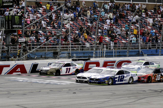 Ryan Blaney (12) narrowly slides by driver Ryan Newman (6) to take the checkered flag in a NASCAR Cup Series auto race at Talladega Superspeedway, Monday, Oct 14, 2019, in Talladega, Ala. (AP Photo/Amanda Newman)
