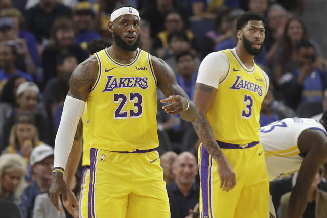 Los Angeles Lakers forward LeBron James (23) reacts in front of forward Anthony Davis (3) during the first half of a preseason NBA basketball game against the Golden State Warriors in San Francisco, Saturday, Oct. 5, 2019. (AP Photo/Jeff Chiu)