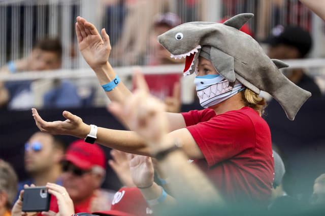 "FILE - In this Sept. 29, 2019, file photo, a fan wears a shark hat as Washington Nationals' Gerardo Parra comes up to bat in the eighth inning of a baseball game against the Cleveland Indians at Nationals Park in Washington. The ""Baby Shark, doo doo doo doo doo doo"" earworm might just be coming to a World Series near you, if Washington Nationals backup outfielder Gerardo Parra heads to the plate during one of his team's home games against the Astros. (AP Photo/Andrew Harnik, File)"