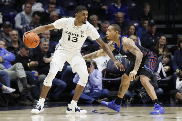 FILE - This Feb. 9, 2019, file photo shows Xavier's Naji Marshall, left, looking to pass against DePaul's Devin Gage, right, during the second half of an NCAA college basketball game, in Cincinnati. Travis Steele made it through a rough first year as Xavier's coach, losing key players to graduation and injury. The Musketeers return their core players and are ranked No. 19 to start his second season. (AP Photo/John Minchillo, File)