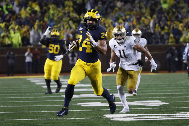 Michigan running back Zach Charbonnet (24) runs for a 35-yard gain as Notre Dame safety Alohi Gilman (11) pursues in the first half of an NCAA college football game in Ann Arbor, Mich., Saturday, Oct. 26, 2019. (AP Photo/Paul Sancya)