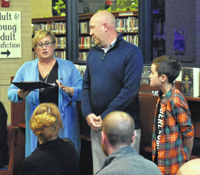 Clinton Massie Middle School Principal Lorinda Ottaway, far left, presents certificates to eighth-grade science teacher James Brady, center, and student Danny Mefford during the student and teacher spotlight at Monday's school board meeting.