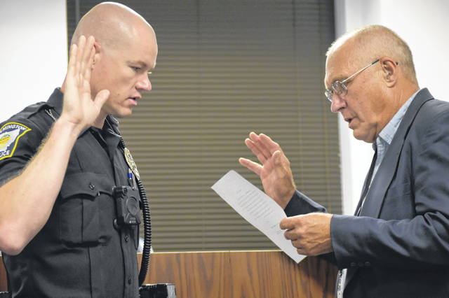 Daniel Hopkins, left, gets sworn in by Mayor John Stanforth as the newest officer of the Wilmington Police Department at Thursday's Wilmington City Council meeting.