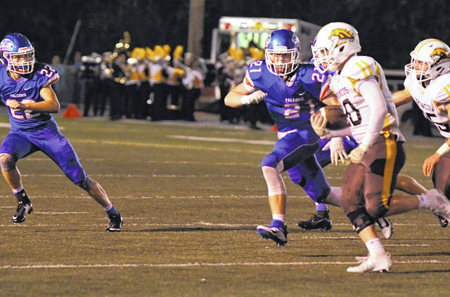 Clinton-Massie's Daelin Maple (21) and Garrett Trampler (22) zero in on a Western Brown ball carrier during Friday night's game at Frank Irelan Field.