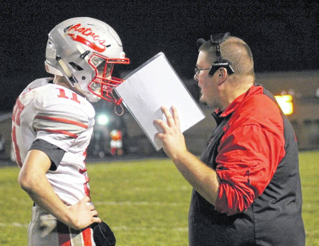 East Clinton head coach Steven Olds (right) gives a play to quarterback Jared Smith during last week's game at Clermont Northeastern.