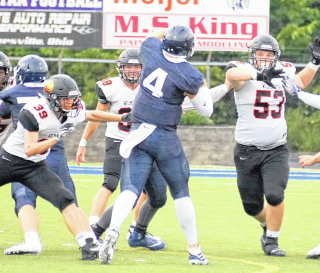 Wilmington's Jeff Valentine (39), Conner Mitchell (38) and Jordan Macik (53) in the opener against Valley View.