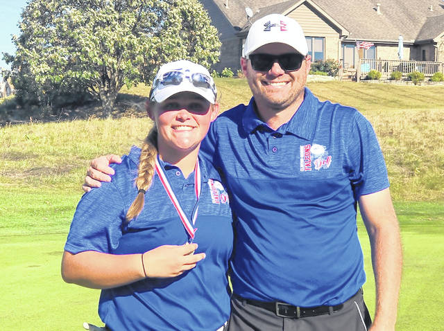 Clinton-Massie senior Gabby Woods and head coach Tim McGraw celebrate Woods' district championship Wednesday at Pipestone Golf Course.