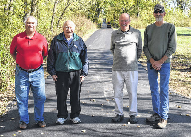 From left, Clinton County Park Commissioner Bob Thobaben, Sabina Mayor Dean Hawk, Bruce Saunders of the Clinton County Trails Coalition, and Village Administrator Rob Dean stand on the newly paved Clinton-Fayette Friendship Trail on Monday.