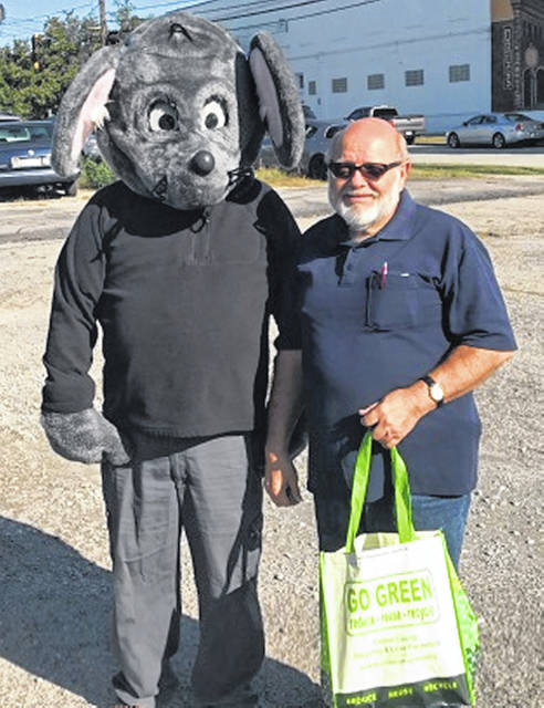 "Congratulations to the first winner in the annual Get Caught Recycling Campaign! Buster the Mouse, from the Clinton County Solid Waste District, caught Mr. Landwehr ""green-handed"" putting the proper recyclables into the community drop-off recycling containers located in Blanchester. For his efforts in practicing the 3-R's, Mr. Landwehr received several recycledcontent prizes, including a reusable shopping tote, hammock, and other such items. Don't miss out on this chance to win great prizes by simply recycling household items such as bottles, jars, and newspapers. For a list of the local recycling drop-off locations and acceptable materials, visit the SWMD's website at www.co.clinton.oh.us/recycling. The Get Caught Recycling Campaign will take place all throughout the month of October, so be on the lookout — you could be the next person caught greenhanded!"