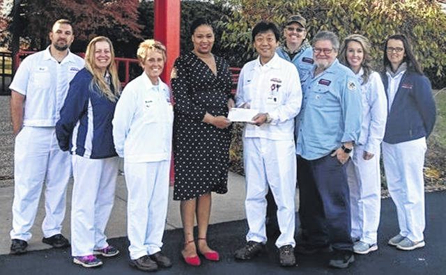 Kazumi Ikeuchi, COO of American Showa's Steering Division, presents a $7,000 donation to Erin Joyner, representative of Volunteers of America Veterans Services program. From left are Brad Brown, Jodelle Stricklett, Brenda Cox, Erin Joyner, Kazumi Ikeuchi, Kevin Mintkenbaugh, Mark Martinez, Jillian Jacobs, and Mellisa Collins.