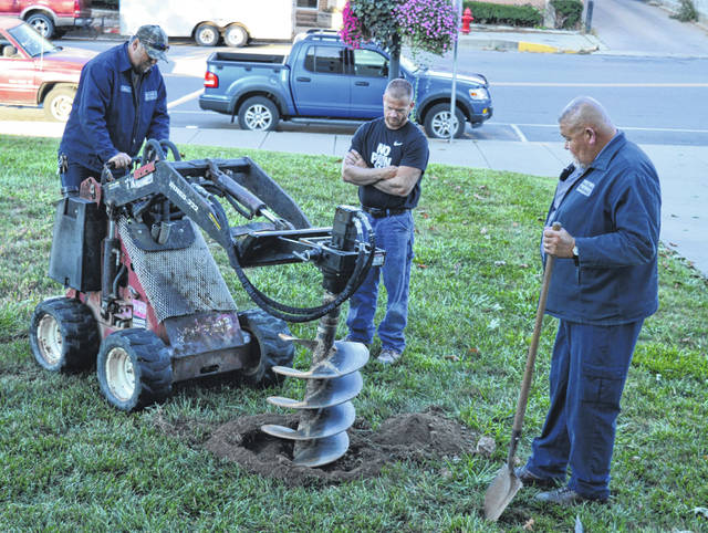 Prior to placing a historical marker that observes the Clinton County Courthouse's 100th anniversary, a hole was drilled for the post.
