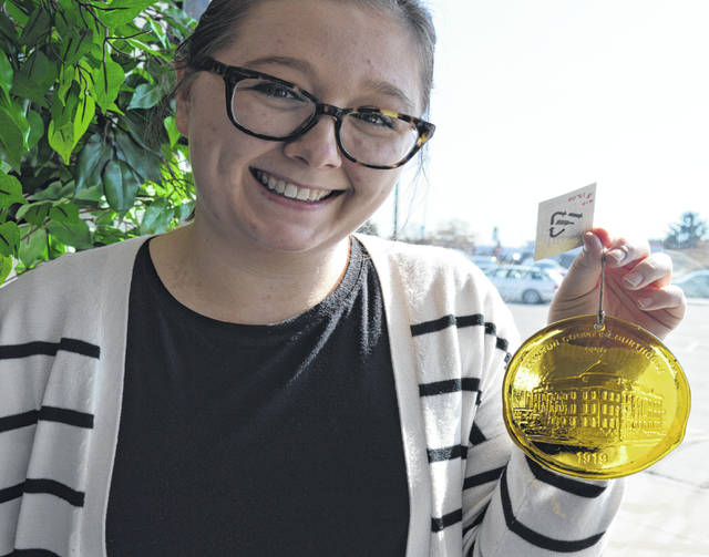 This 100-percent recycled glass sun catcher is a Clinton County Courthouse centennial souvenir, and they will be available to purchase on Saturday at the celebration at the courthouse. Displaying the amber sun catcher is Clinton County Historical Society Executive Director Shelby Boatman.