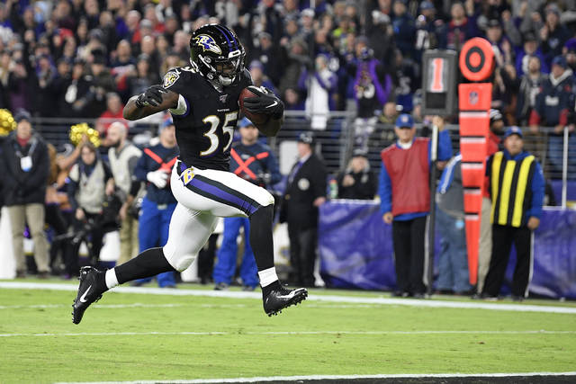 Baltimore Ravens running back Gus Edwards (35) scores on a touchdown run against the New England Patriots during the first half of an NFL football game, Sunday, Nov. 3, 2019, in Baltimore. (AP Photo/Nick Wass)
